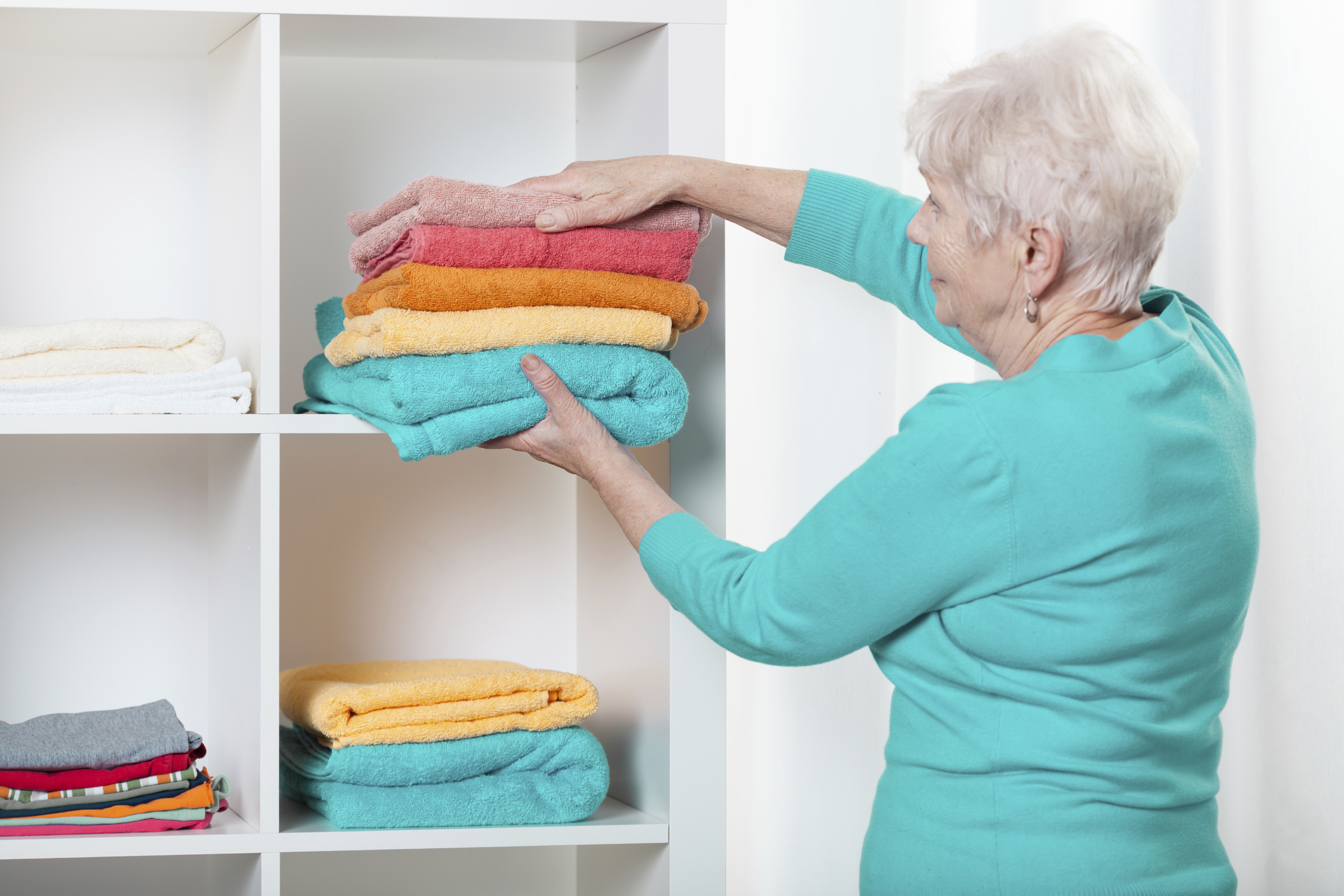 Woman putting towels to the shelf - Autumn Leaves