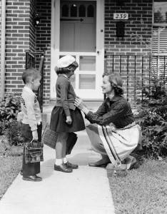 Mother outside front door, buttoning sweater of daughter going off to school with her brother. (Photo by H. Armstrong Roberts/Retrofile/Getty Images)