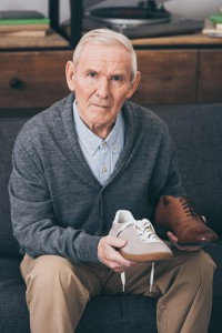 retired man choosing between classic and modern shoes