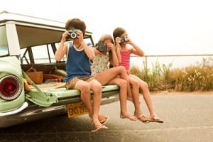 Three children sitting on back of estate car taking photographs