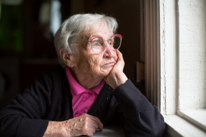 Elderly woman in glasses thoughtfully looking out the window.